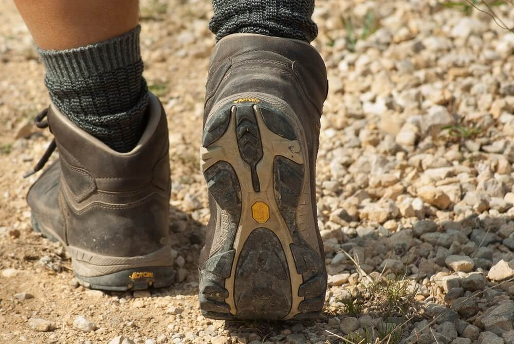 man wearing hiking boots walking on the ground, Spain packing list