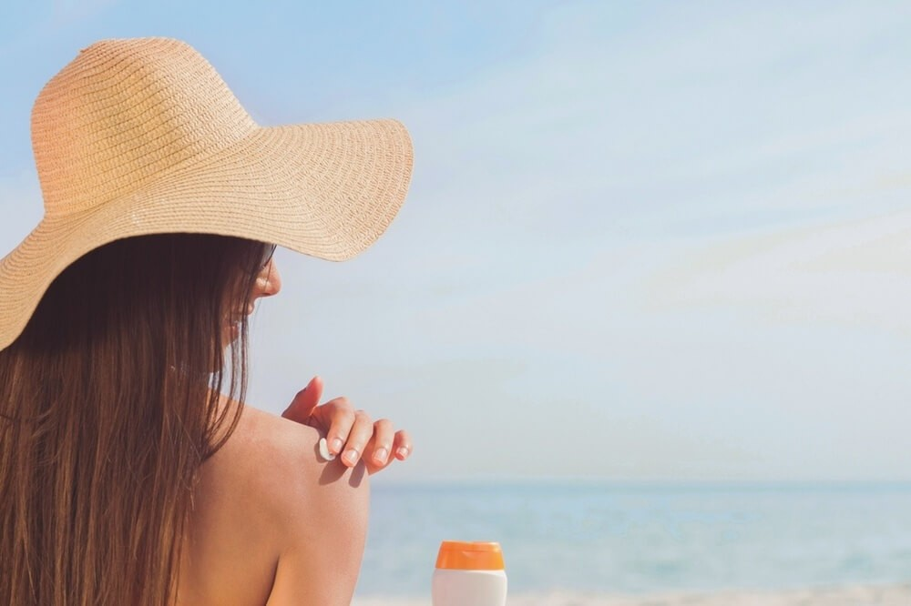 Lady putting a sunscreen on her sholder on the beach