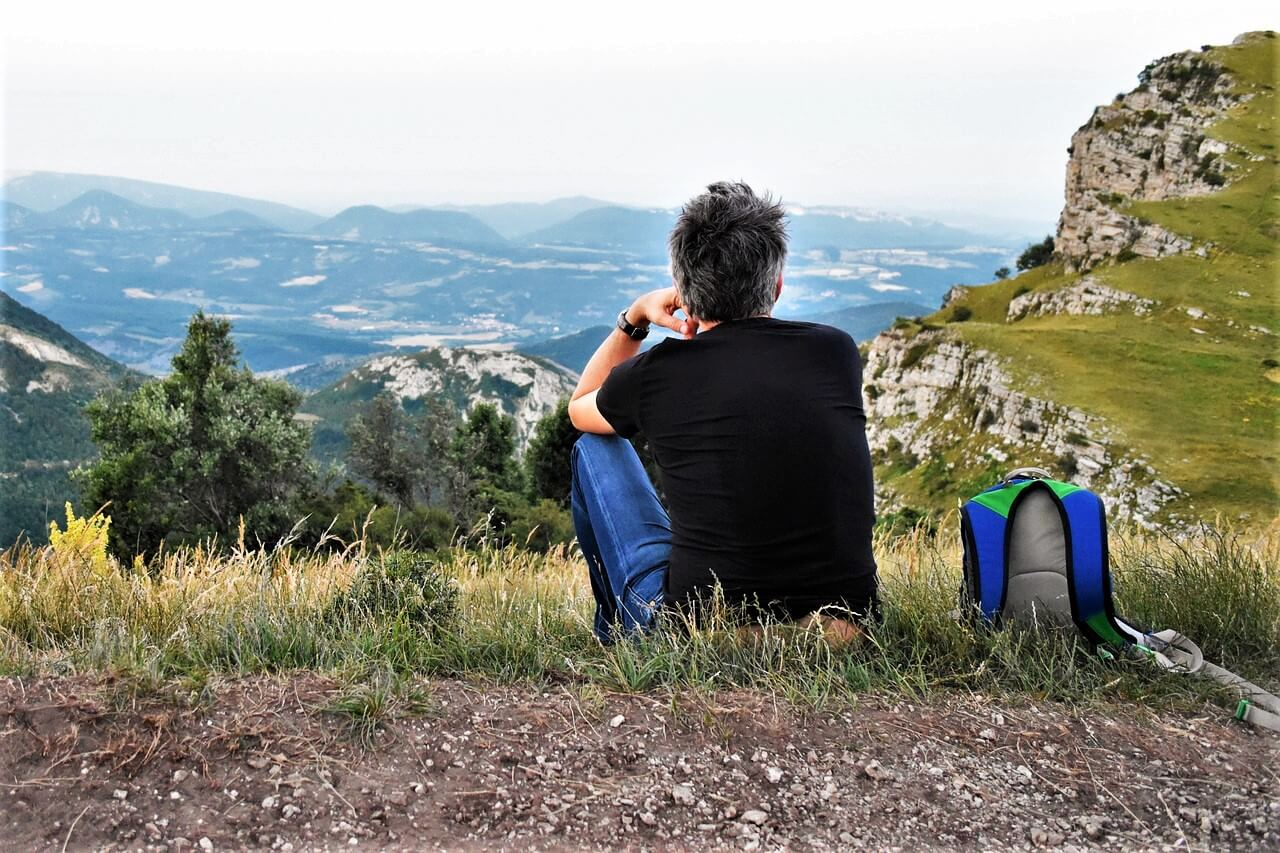 traveler enjoying the moment while traveling sitting on the mountain