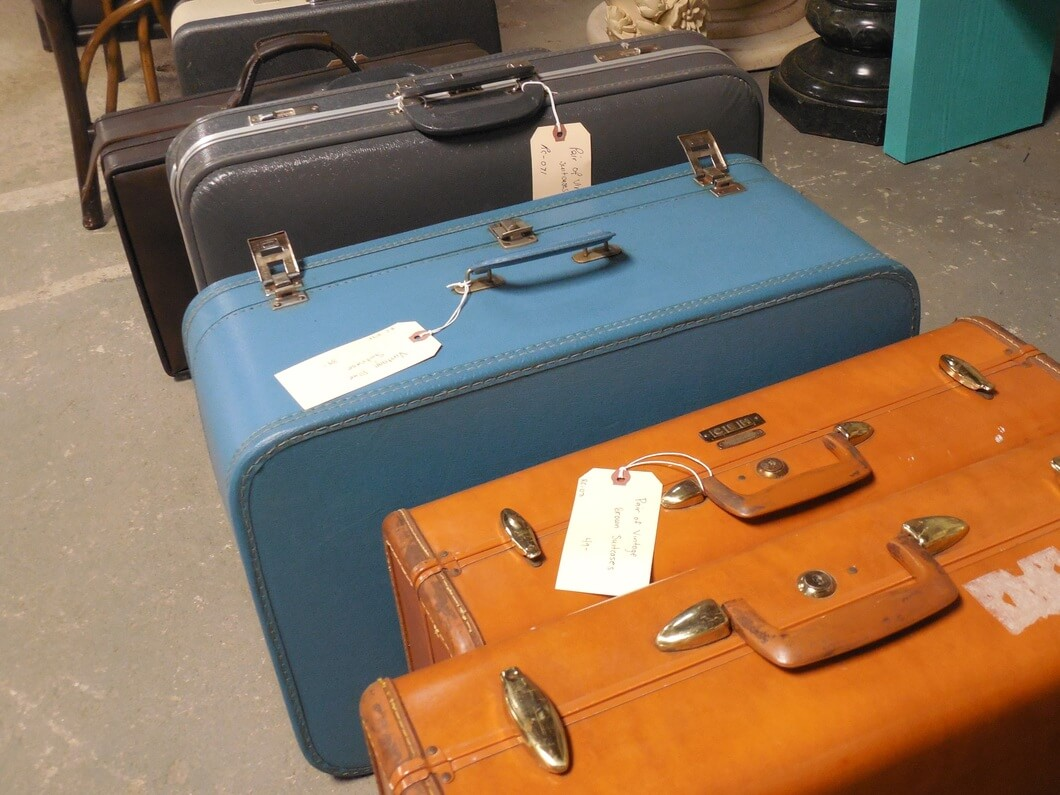 Vintage carry-on luggage with items to pack for a flight