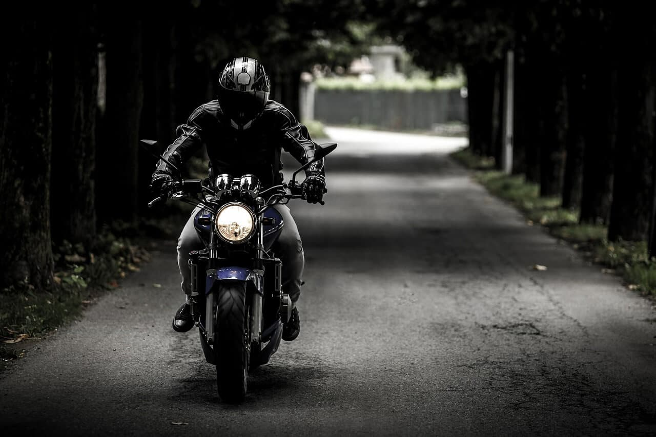 biker riding a cruiser on a dark road, protection motorcycle gear