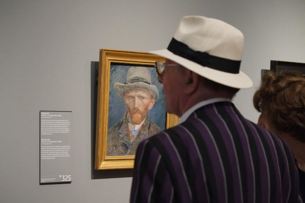 Person in Van Gogh Museum near self portrait, Amsterdam itinerary