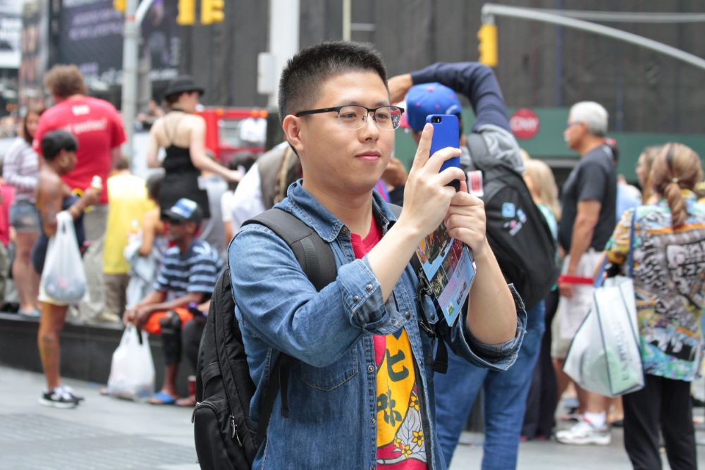 Chinese young tourist visiting New York City taking pictures of sights