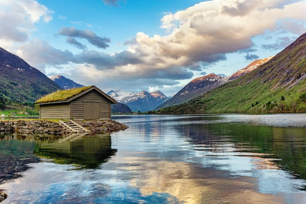 Summer view of Norway fjords, mountains and wooden house