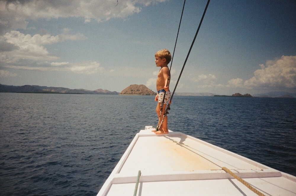 Small kid on a sailing boat in the sea