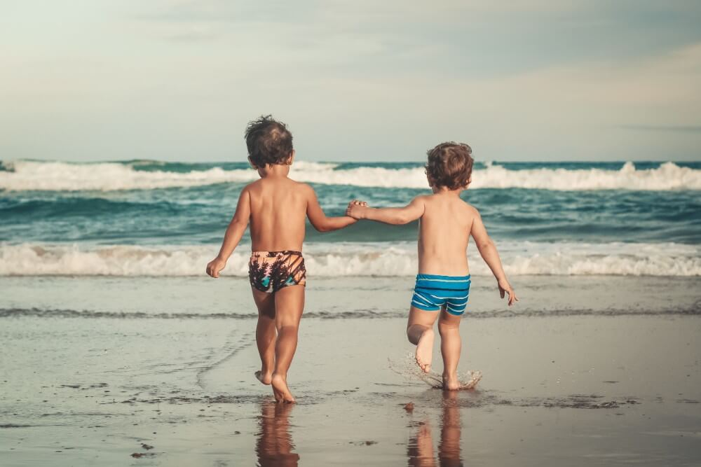 Small boys playing on the beach holding hands near the ocean