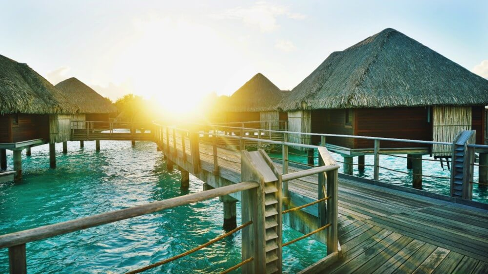 Traditional Indonesian houses in water on sunset in Bora Bora